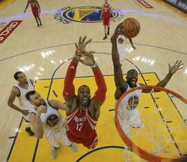 Golden State Warriors Draymond Green and Houston Rockets Dwight Howard fight for a rebound in Game 5 of the NBA Playoffs at Oracle Arena on Wednesday, April 27, 2016 in Oakland, Calif.