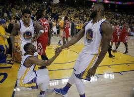 Brandon Rush (4) and Festus Ezeli (31) help Ian Clark (21) off the floor after he fell on the Rockts last possession with time expired as the Golden State Warriors played the Houston Rockets in Game 5 of the first round of the Western Conference playoffs at Oracle Arena in Oakland, Calif., on Wednesday, April 27, 2016. The Warriors won 114-81, to advance to the second round.