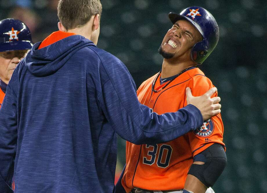 A trainer comes to the aid of Houston Astros' Carlos Gomez, who was hit by a pitch from Seattle Mariners' Hisashi Iwakuma during the fourth inning of a baseball game Wednesday, April 27, 2016, in Seattle. (Dean Rutz/The Seattle Times via AP) Photo: Dean Rutz, MBR / The Seattle Times