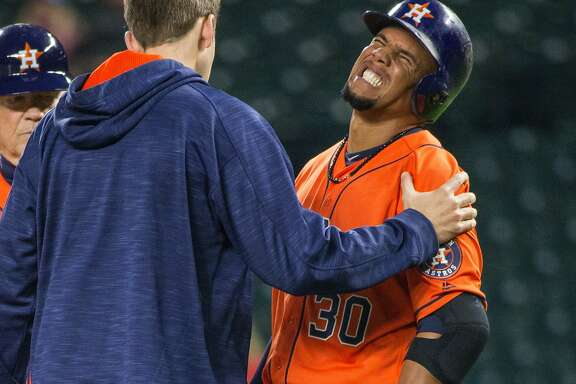 A trainer comes to the aid of Houston Astros' Carlos Gomez, who was hit by a pitch from Seattle Mariners' Hisashi Iwakuma during the fourth inning of a baseball game Wednesday, April 27, 2016, in Seattle. (Dean Rutz/The Seattle Times via AP)