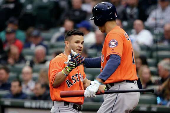 Houston Astros' Jose Altuve, left, is congratulated on his home run against the Seattle Mariners by Carlos Correa in the first inning of a baseball game Wednesday, April 27, 2016, in Seattle. (AP Photo/Elaine Thompson)