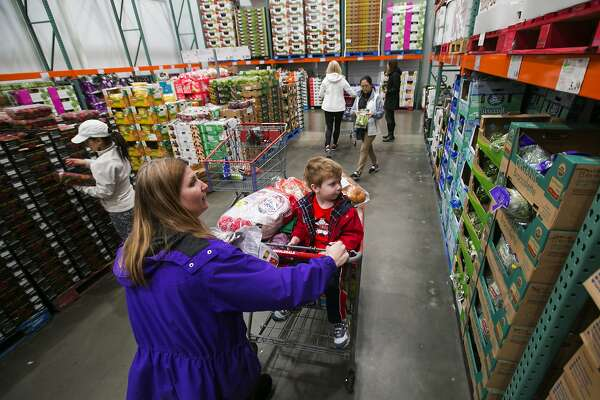Kimberly Fee pushes a shopping cart holding her son, Cameron, 4, at Costco in Issaquah, Wash. Costco is working to boost its supply of organics. (Bettina Hansen/The Seattle Times/TNS)