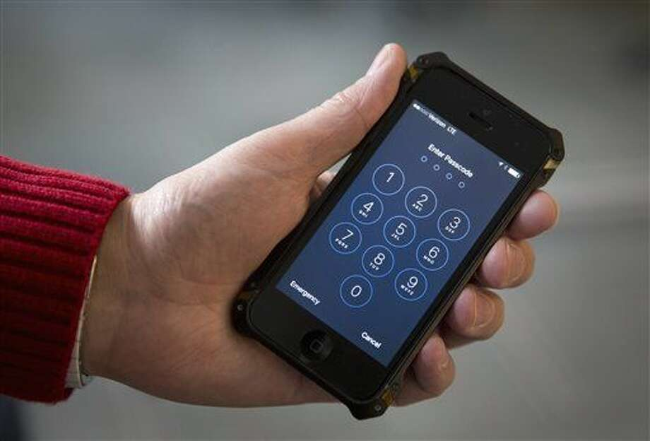 FILE - In this Feb. 17, 2016 file photo shows an iPhone in Washington. A schism has emerged among family members of victims and survivors of the San Bernardino, California terrorist attack, with at least a couple supporting Apple Inc. in its battle against a federal court order to help the FBI hack into a shooter's locked iPhone. (AP Photo/Carolyn Kaster)