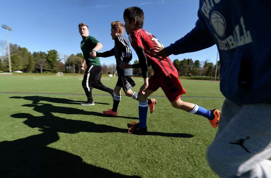 Player Todd Jensen, left, leads kids during morning drills at the soccer camp put on by the Skidmore College varsity soccer teams and the Student Athletic Advisory Committee Thursday April 28, 2016 at athletic field on the campus in Saratoga Springs, N.Y.     (Skip Dickstein/Times Union) Photo: SKIP DICKSTEIN / 10036396A