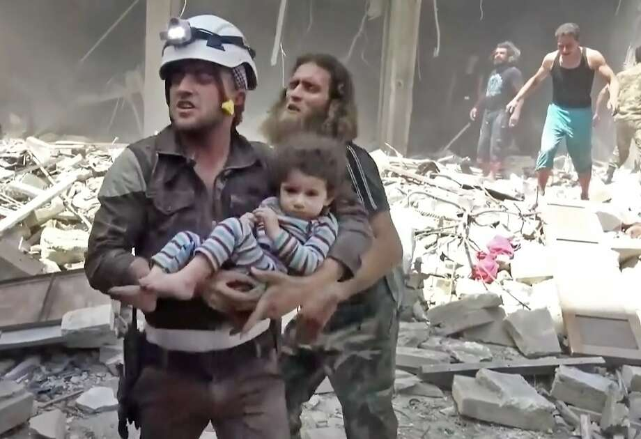 A Civil Defense worker carries a child after air strikes hit Aleppo. First responders say the new violence brings the death toll in the past 24-hours in the deeply divided city to at least 60 killed. Photo: Associated Press