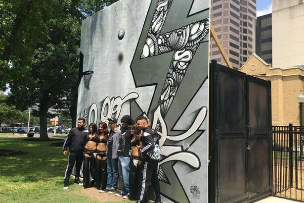 Artist Nik Soupe and Shek Vega stand alongside the Spurs Silver Dancers at the unveiling of the newest Silver and Black-inspired mural at Travis Park on April 28, 2016.