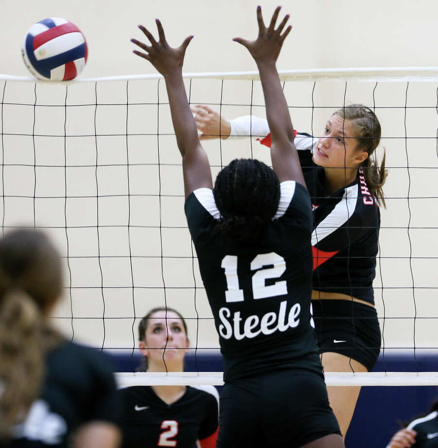 Churchill's Taylor Martinez (right) hits the ball past Steele's Tisharra Thompson during their UIL Class 6A first-round volleyball playoff match at Alamo Convocation Center on Tuesday, Nov. 4, 2014.  MARVIN PFEIFFER/ mpfeiffer@express-news.net Photo: MARVIN PFEIFFER, STAFF / San Antonio Express-News / Express-News 2014