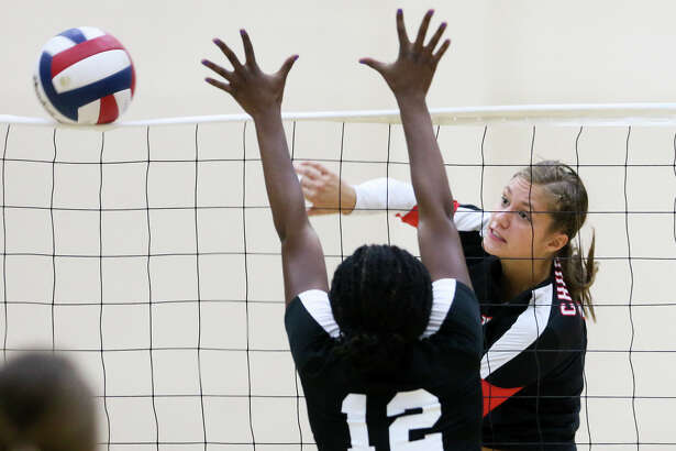 Churchill's Taylor Martinez (right) hits the ball past Steele's Tisharra Thompson during their UIL Class 6A first-round volleyball playoff match at Alamo Convocation Center on Tuesday, Nov. 4, 2014.  MARVIN PFEIFFER/ mpfeiffer@express-news.net