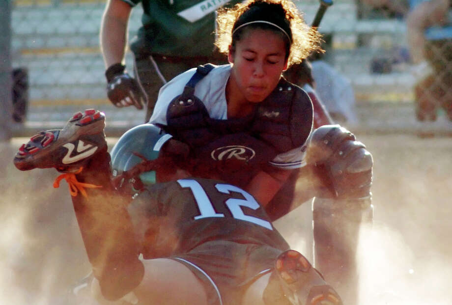 Reagan pinch runner Jean Rodriguez (12) is tagged out at home by Smithson Valley catcher Nikki Salazar on April 12, 2005 at North East Softball Complex. Photo: Express-News File Photo / SAN ANTONIO EXPRESS NEWS