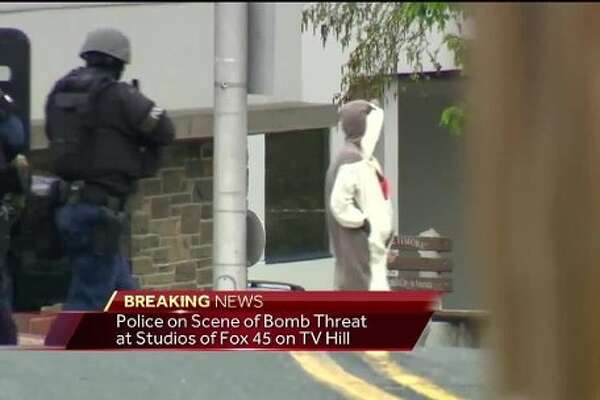 WBAL-TV 11 News learned that a man dressed in a onesie with a surgical mask and sunglasses covering his face entered the TV station's front entrance. The man left the building and wouldn't take hands out of pockets, police said. The man has some type of device in his hand,  so a counter-sniper shot him, police said.