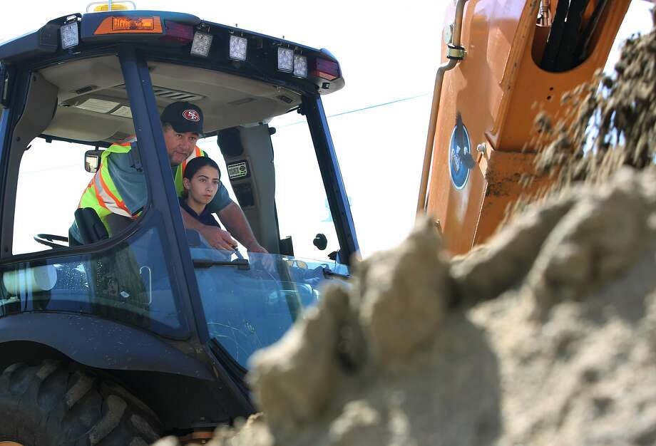 Pat Meagher shows elementary students, including Ella Schwartz, 10, how to operate a backhoe. Photo: Liz Hafalia, The Chronicle