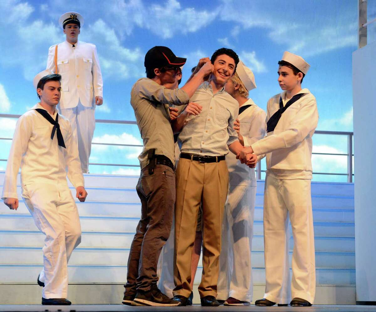 Tyler Ponath, a audio technician, fixes the mic of Benjamin Freedman, who plays Billy Crocker during a dress rehearsal for Westhill's 'Anything Goes' at Westhill High School .