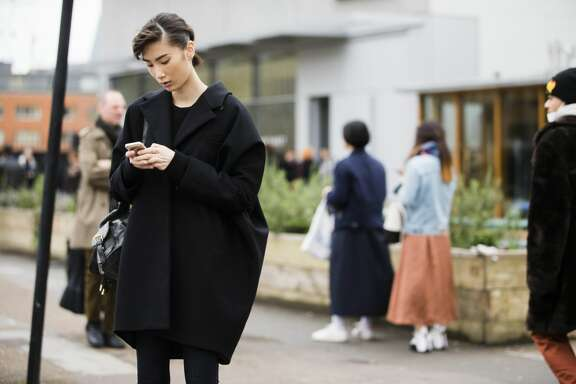 Chinese model Dylan Xue checks her phone and ewars an oversized minimalist black coat at the Margaret Howell show during London Fashion Week Autumn/Winter 2016/17  on February 21, 2016 in London, England.