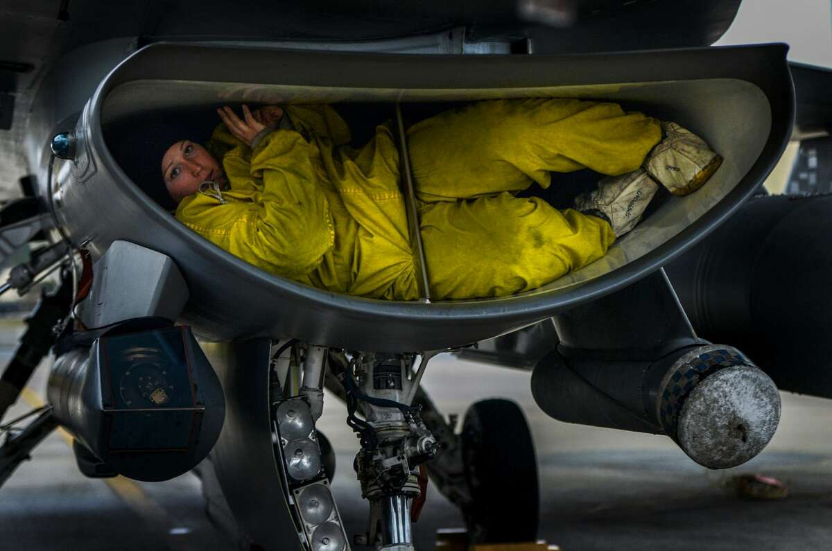 A U.S. Air Force crew chief assigned to the 77th Fighter Squadron, crawls out of the intake of an F-16 Fighting Falcon as she completes her post flight inspection on the aircraft, Jan. 15, 2015, Shaw Air Force Base, S.C. Crews chiefs work around the clock to keep Shaw's fleet of F-16 Fighting Falcons mission ready at all times.
