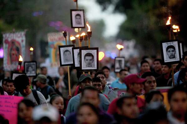 In December, relatives of the 43 missing students from the rural teachers college march holding pictures of their missing loved ones during a protest in Mexico City. A new report points in the direction of collusion by municipal, state and federal law enforcement in the incident.