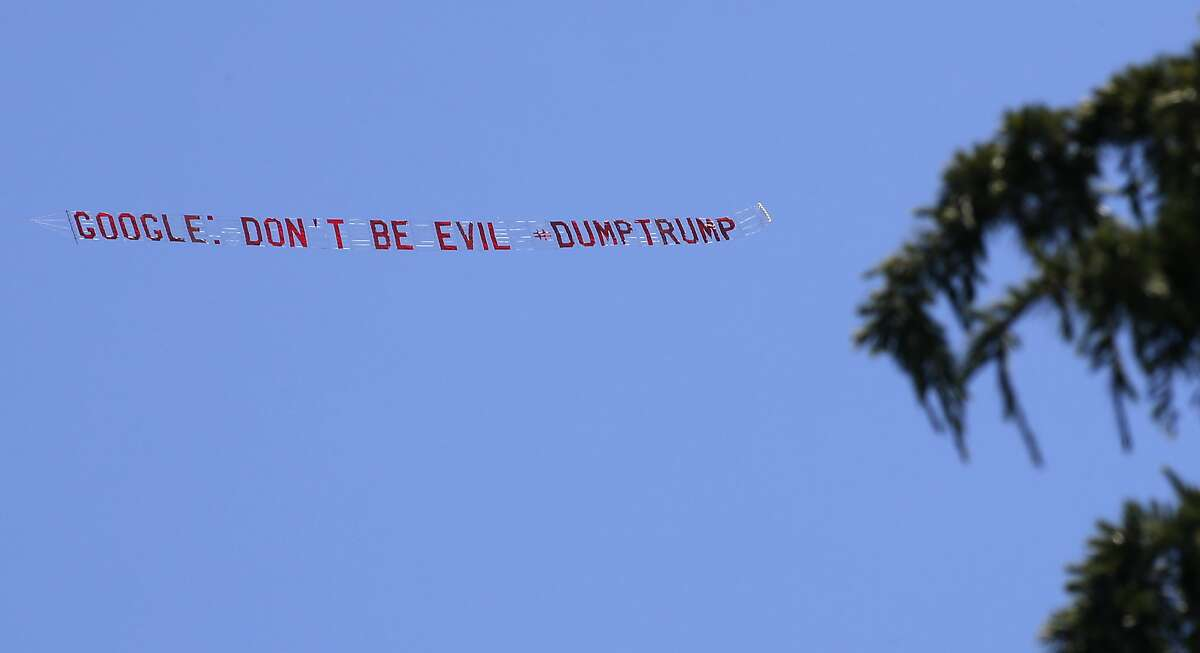 An plane circles above the headquarters of Google dragging behind it a message in Mountain View, California on Thurs. April 28, 2016.