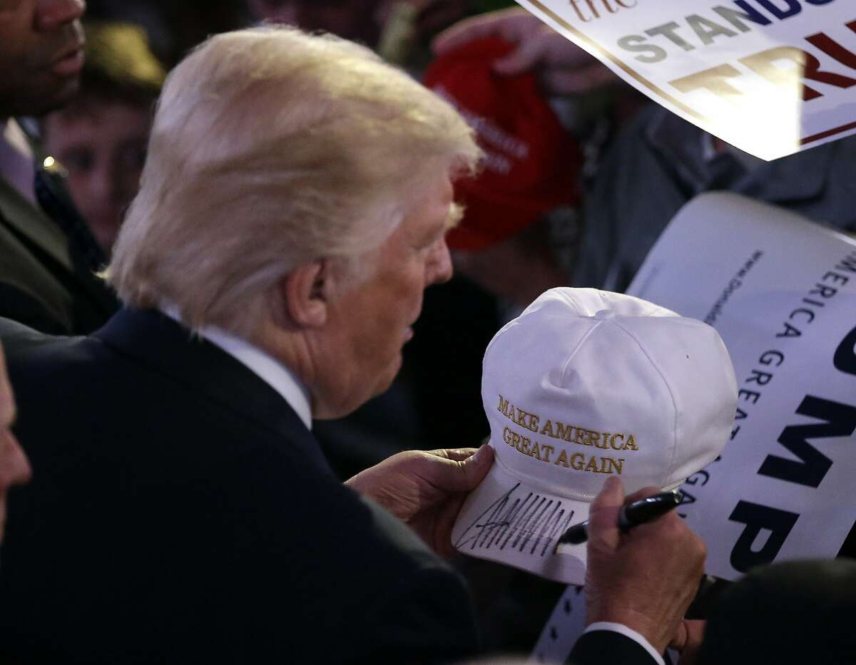 Republican presidential candidate Donald Trump autographs a hat during a campaign stop Wednesday, April 27, 2016, in Indianapolis. (AP Photo/Darron Cummings)
