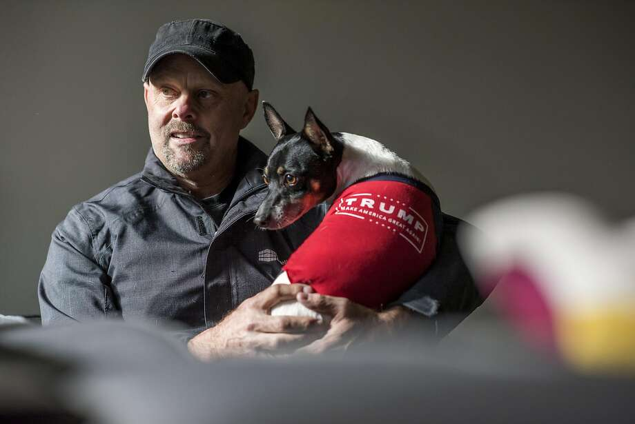 Alan Burradell, a Donald Trump supporter, holds his dog Django while sitting for a photograph in San Francisco, California, U.S., on  Wednesday, April 27, 2016. Photo: David Paul Morris, Bloomberg