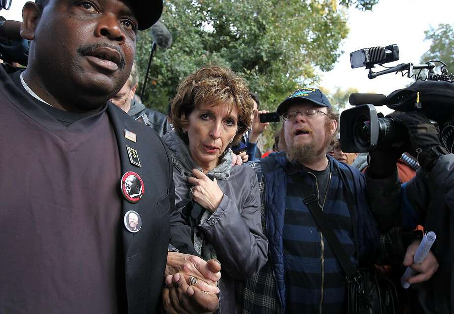 UC Davis Chancellor Linda Katehi (center) is escorted to a car during 2011 demonstrations on the UC Davis campus, where police pepper-sprayed a group of peaceful student protesters. Photo: Justin Sullivan, Getty Images