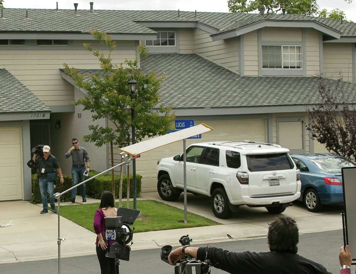 Members of the media stand outside the home of Syed Raheel Farook, the elder brother of San Bernardino gunman Syed Rizwan Farook, after the FBI served a warrant to the location, in Corona, Calif., Thursday, April 28, 2016. Syed Raheel Farook was arrested with two others Thursday in what prosecutors say was a marriage scheme to fraudulently allow one of them to remain in the United States. (AP Photo/Damian Dovarganes)