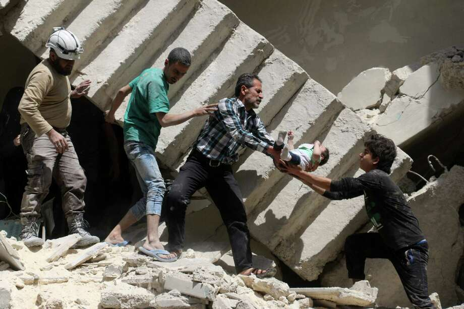 Rescuers remove a baby from under the rubble of a destroyed building following an air strike on the rebel-held neighborhood of al-Kalasa in the northern Syrian city of Aleppo on Thursday. Photo: AMEER ALHALBI, Stringer / AFP or licensors