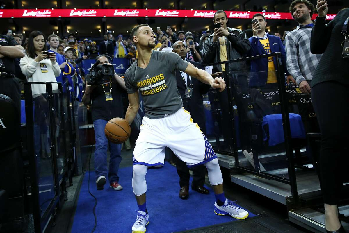 Golden State Warriors' Stephen Curry tries to make a shot from tunnel before NBA game against San Antonio Spurs at Oracle Arena in Oakland , Calif., on Monday, January 25, 2016.