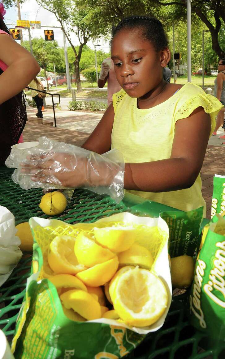 Rajah Williams, 10, slices fresh lemons during Lemonade Day 2015 at the Farmers Market on Navigation. Young business owners learn the basics of taking a loan, building a business and managing the finances.