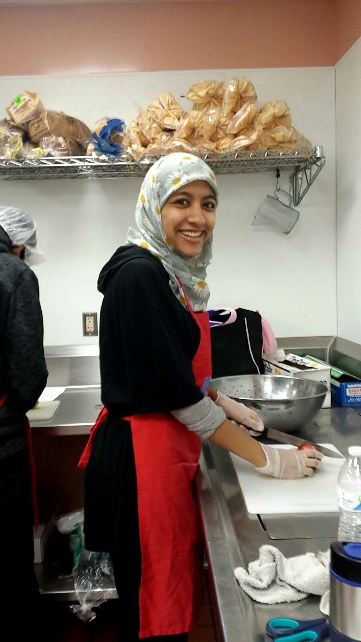 A volunteer with the Muslim Soup Kitchen Project prepares a meal for local homeless and needy people in this 2015 photo. They will participate in the inaugural National Muslim Soup Kitchen Day on Saturday at nine local sites. (Photo courtesy of Uzma Popal)