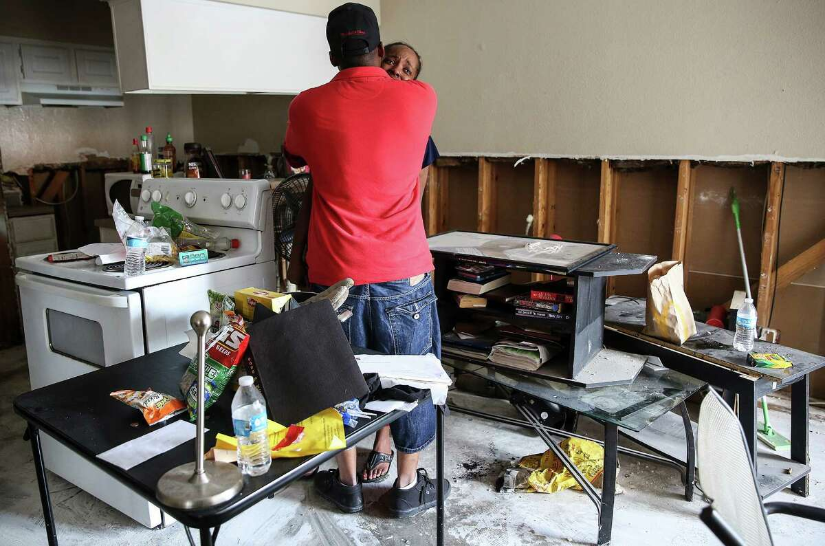 Eric Collins comforts his girlfriend, Yourlette Mack, in their flood-damaged apartment at Salado at Cityview.