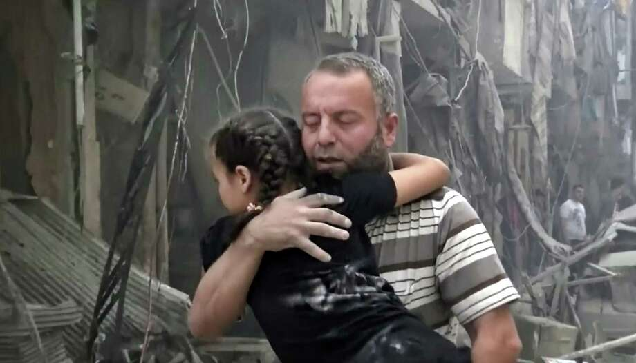 In this image made from video and posted online from Validated UGC, a man carries a child after airstrikes hit Aleppo, Syria, Thursday, April 28, 2016. A Syrian monitoring group and a first-responders team say new airstrikes on the rebel-held part of the contested city of Aleppo have killed over a dozen people and brought down at least one residential building. The new violence on Thursday brings the death toll in the past 24-hours in the deeply divided city to at least 61 killed. (Validated UGC via AP video) ORG XMIT: CAINM112 / Validated UGC