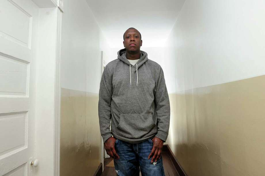 Terell Reid, of Bridgeport, stands in his apartment on Thursday. Reid, who is on parole, has landed a job. Photo: Christian Abraham / Hearst Connecticut Media / Connecticut Post