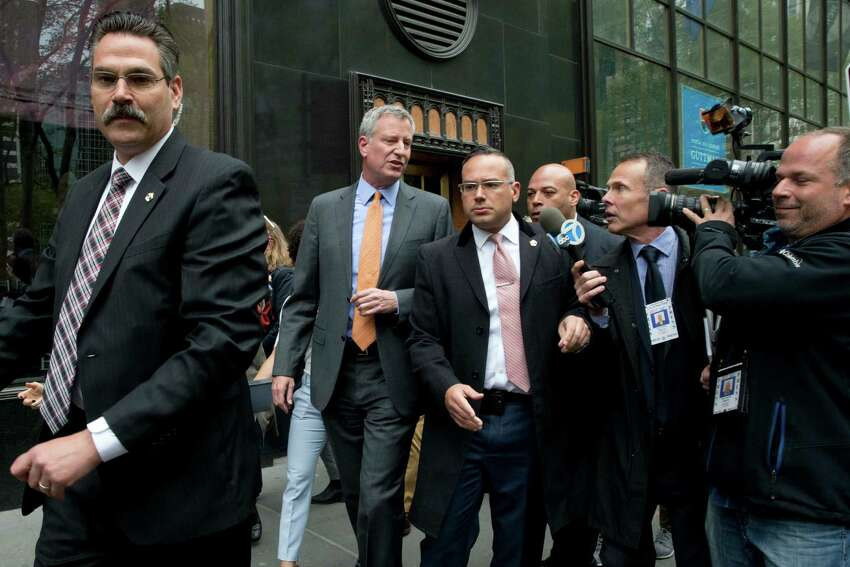 New York City Mayor Bill de Blasio, second from left, is surrounded security and followed by reporters as he leaves an event, Thursday, April 28, 2016, in New York. Aides to de Blasio have been subpoenaed by state and federal prosecutors amid investigations into his campaign fundraising operation, his administration said. (AP Photo/Mary Altaffer) ORG XMIT: NYMA102