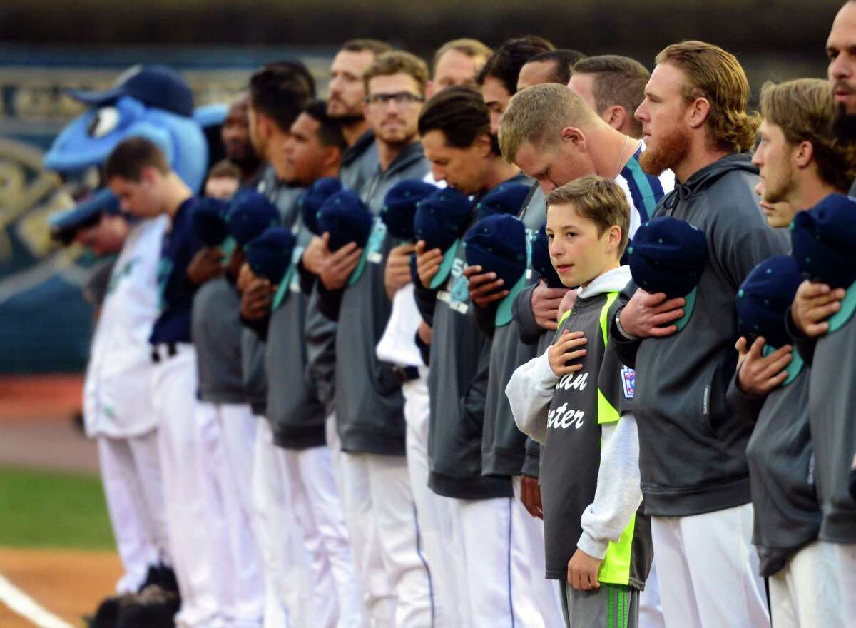Above, Curtis Tenney, who plays Little League baseball with the Italian Center of Stamford team, stands with the Bridgeport Bluefish lineup during the singing of the Star Spangled Banner before the start of the opening day game between the Bluefish and the New Britain Bees at the Ballpark at Harbor Yard in Bridgeport on Thursday. At right, Matt Tabet, 11, of Wilton, yells as he tries to get a ball during the game.