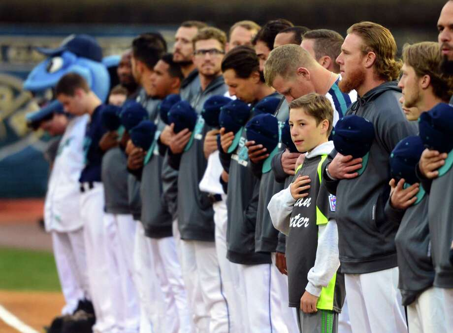 Above, Curtis Tenney, who plays Little League baseball with the Italian Center of Stamford team, stands with the Bridgeport Bluefish lineup during the singing of the Star Spangled Banner before the start of the opening day game between the Bluefish and the New Britain Bees at the Ballpark at Harbor Yard in Bridgeport on Thursday. At right, Matt Tabet, 11, of Wilton, yells as he tries to get a ball during the game.  Photo: Christian Abraham / Hearst Connecticut Media / Connecticut Post
