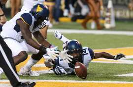 West Virginia safety Karl Joseph (8), left, recovers the ball in the end zone against Baylor during the first half of an NCAA college football game on Saturday, Oct.  5, 2013, in Waco, Texas. West Virginia is cornerback Ricky Rumph (14) looks on. (AP Photo/Michael Bancale)