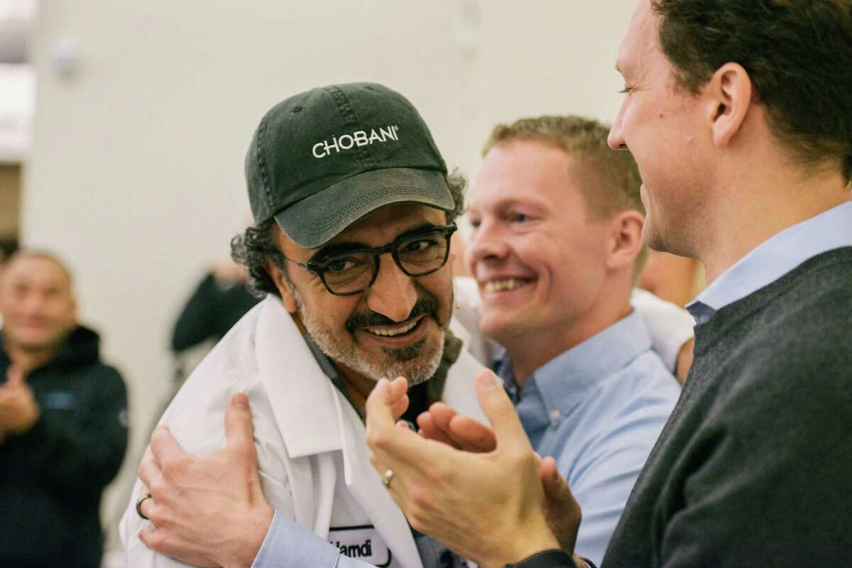 Hamdi Ulukaya, left, a Turkish immigrant who founded the yogurt company Chobani in 2005, during an announcement that he would give employees shares worth up to 10 percent of the company when it goes public or is sold, in New Berlin, N.Y., April 26, 2016. The ownership stake in the yogurt company could make some of the 2,000 full-time employees into millionaires. (Alexandra Hootnick/The New York Times)