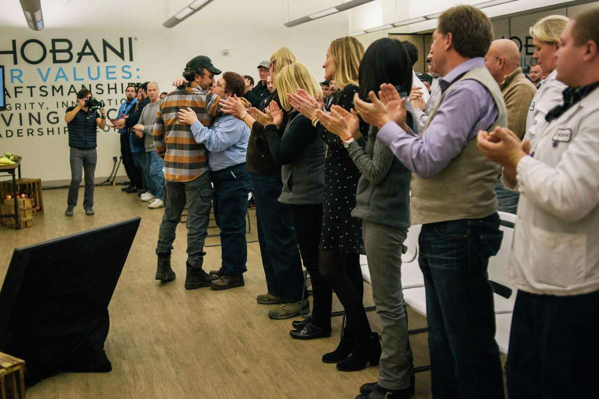 Hamdi Ulukaya, the founder of Chobani, is applauded by employees after announcing that he was giving them shares worth up to 10 percent of the company, in New Berlin, N.Y., April 26, 2016. The ownership stake in the yogurt company could make some of the 2,000 full-time employees into millionaires. (Alexandra Hootnick/The New York Times)