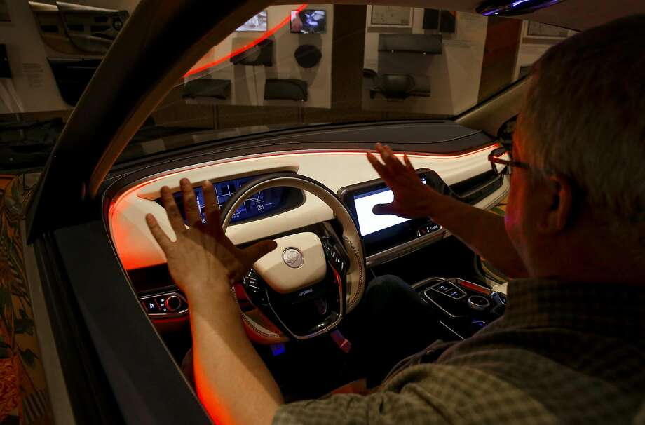 David Muyres demonstrates how red lights illuminate as the vehicle designed by Yanfeng Automotive Interiors is switched to autonomous mode. Below: There are several controls overhead. Photo: Michael Macor, The Chronicle