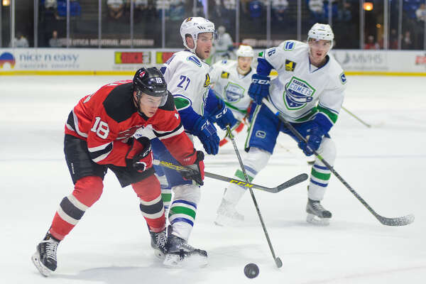 Blake Pietila, left, playing his first game of the series, made an immediate impact for the Albany Devils against the Utica Comets. Here he skates past Taylor Fedun, center, and Joseph LaBate. (Lindsay A. Mogle / Utica Comets)