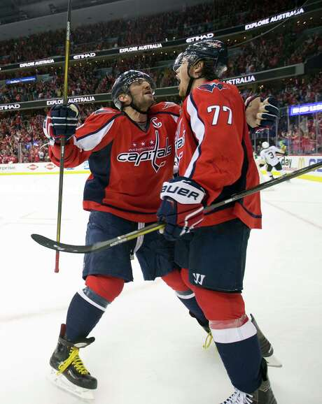 Washington right wing T.J. Oshie, right, celebrates one of his three goals with Alex Ovechkin (8). Photo: Pablo Martinez Monsivais, STF / Associated Press Wash DC