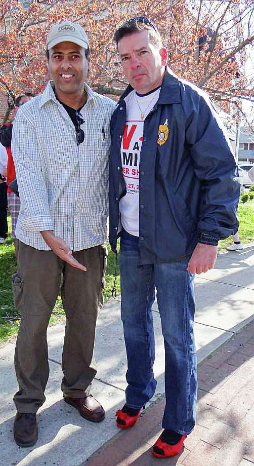 "Police Chief Gary MacNamara, right, sporting red stiletto heels, with Lt. James Perez, will step out to lead Saturday's ""Walk a Mile in Her Shoes"" fundraiser through downtown to benefit the Center for Family Justice. Photo: File Photo / Fairfield Citizen"