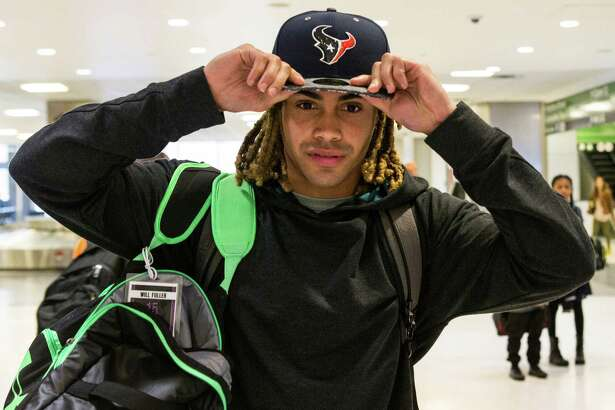 Houston Texans top draft pick, Notre Dame wide receiver Will Fuller, dons his new Texans hat as he walks through baggage claim at George Bush Intercontinental Airport on Friday, April 29, 2016, in Houston.