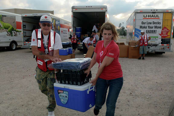 American Red Cross Disaster Service's Larry Martens, left, of Welcome Home, Arkansas; and Shawna Besse-Stout, of Knoxville, Tennessee; load water and supplies to vehicles of residents impacted by the recent flooding in north Houston.