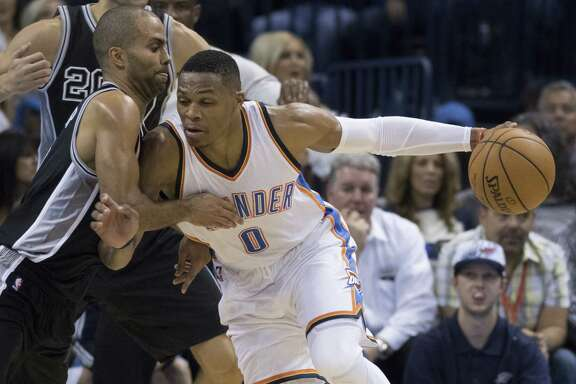 Russell Westbrook of the Oklahoma City Thunder drives against Tony Parker of the San Antonio Spurs as he rebounded a ball during the third quarter of a NBA game at the Chesapeake Energy Center on Oct. 28, 2015.