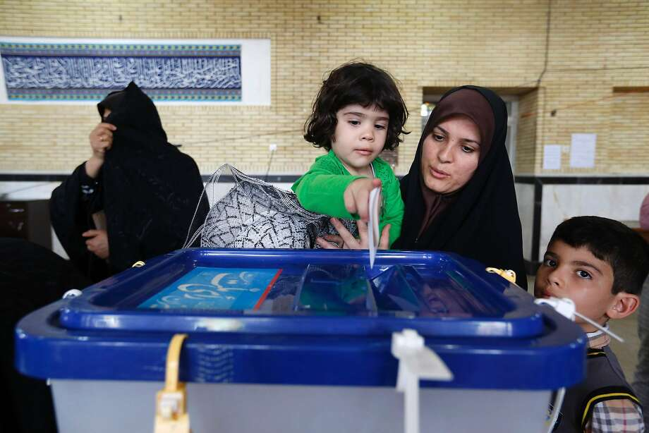 An woman holds a child as she votes in the town of Robat Karim, southwest of the capital ,Tehran. Photo: ATTA KENARE, AFP/Getty Images