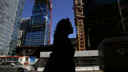 Pedestrians walk past the construction site of Salesforce Tower April 28, 2016 in San Francisco, Calif.