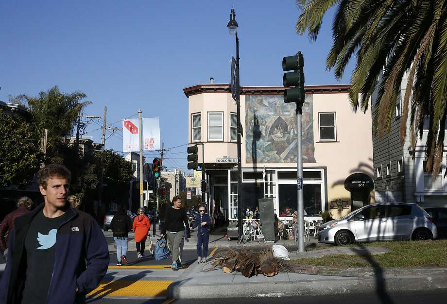 Pedestrians cross Dolores Street, which offers ample evidence of a changing city. Photo: Leah Millis, The Chronicle