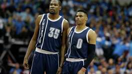 Oklahoma City Thunder forward Kevin Durant (left) and guard Russell Westbrook watch a free throw during the first half in Game 3 of a first-round playoff series against the Mavericks on April 21, 2016, in Dallas.