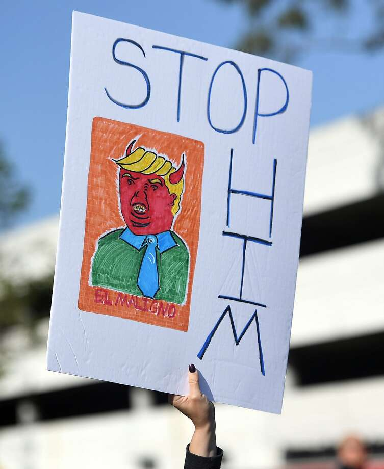 A protester holds up a sign during a rally against US Republican presidential candidate Donald Trump in Burlingame, California on April 29, 2016.  Trump is delivering the keynote address at the California Republican Party's CAGOP 2016 Convention in Burlingame. / AFP PHOTO / Josh EdelsonJOSH EDELSON/AFP/Getty Images Photo: JOSH EDELSON, AFP/Getty Images
