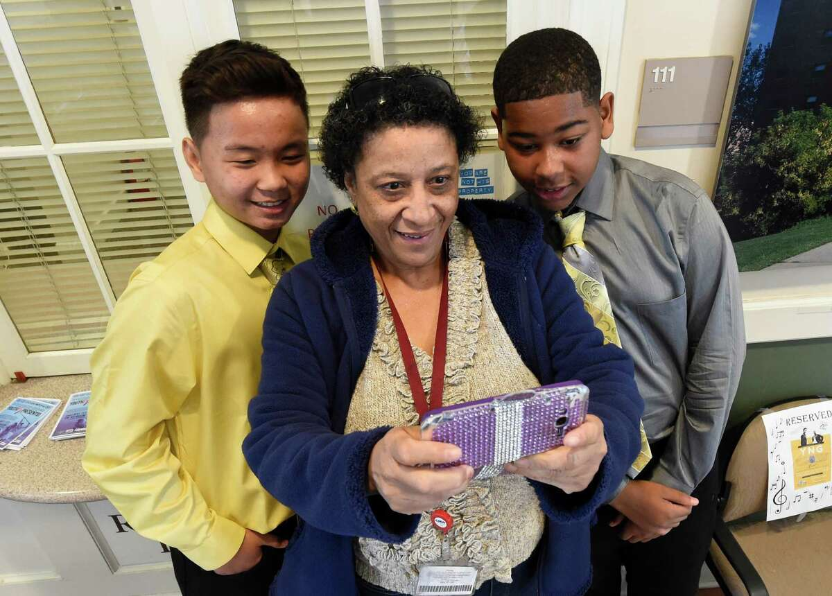 The Albany hip-hop/R&B duo of Rah-mene McDuffie, and Lee Reh, left, aka Young Nobel Gentlement pose for pictures with Vikki Williams, center at the Albany Housing Authority office after their appearance Friday afternoon April 28, 2016 in Albany, N.Y. (Skip Dickstein/Times Union)